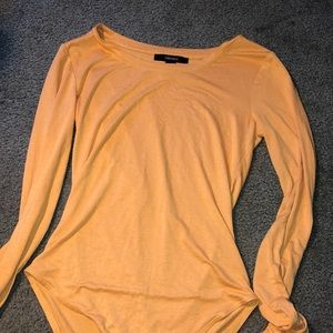 A long sleeve yellow/gold body suit